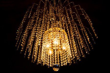 chandelier background: a crystal chandelier glows with golden light on dark background Stock Photo