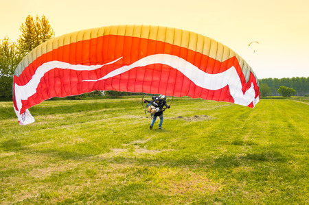 motorized: man with red motorized paraglider takes off from a green field Stock Photo