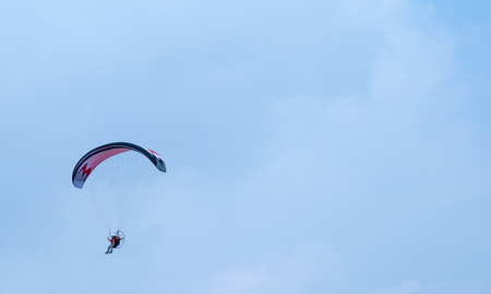 motorized: motorized paraglider flying in the blue sky