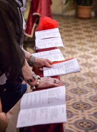 leer biblia: leer el folleto durante un servicio religioso