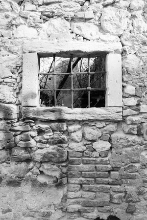 old house window: old window grille of a ruined castle in Italy