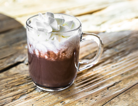 chocolate drink with whipped cream in transparent cup on rough wooden table