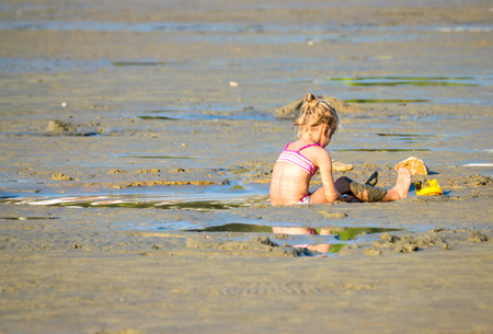 desolation: Little girl playing at the beach during low tide.