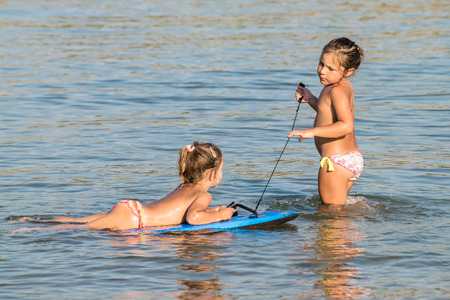 play of color: Two little girls playing in the sea with a floating board. Stock Photo