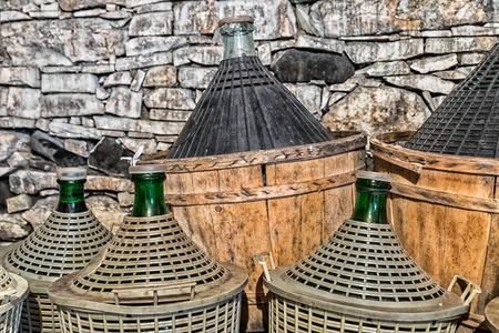 demijohn: Demijohns of wine in a stone cellar. Stock Photo