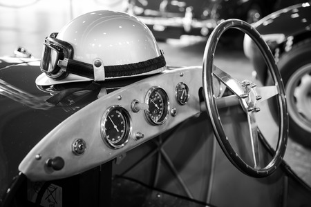 helmet and glasses resting on a old vintage sports car Фото со стока