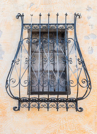 grate of a covered window of an ancient monastery Foto de archivo