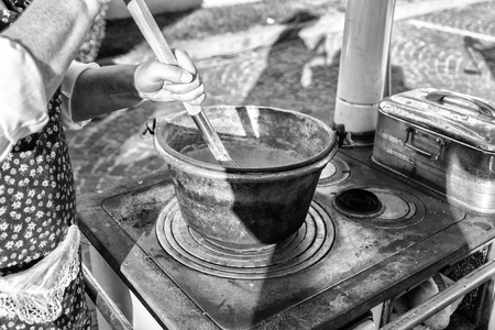 Cooking polenta in a copper pot on wood stove (dish of the Venetian tradition, Italy). Reklamní fotografie