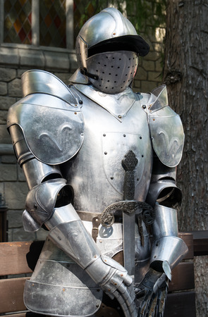 medieval sword: Medieval armor in front of the entrance to a castle. Stock Photo