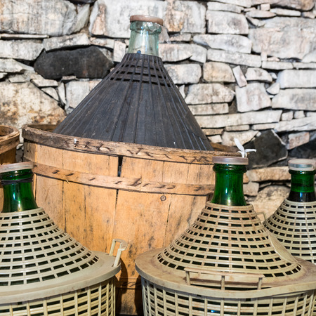 Demijohns of wine in a stone cellar. Stock Photo