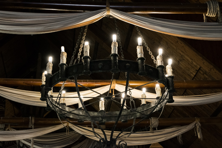 iron curtains: Round iron chandelier in an old tavern. Stock Photo