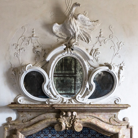 fireplaces: Ornamental mirror above the fireplace of a Venetian villa with sculpture of a phoenix.