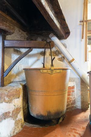 under fire: Crisol de cobre bajo los cuales se encendió un fuego, utilizado para producir queso ricotta. Foto de archivo