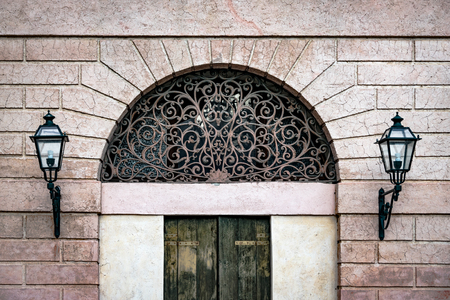 old window: Facade of an ancient Italian villa with artistic iron grill handmade. Stock Photo