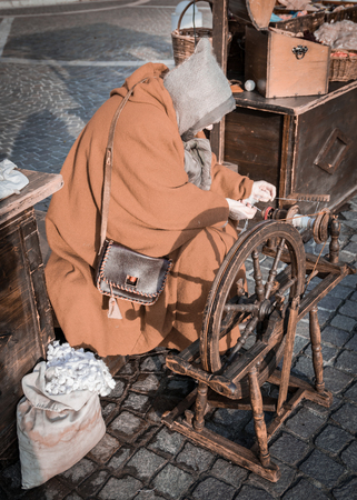 wheel spin: Elderly woman uses the cocoons of silkworms to spin using an old spinning wheel of wood.