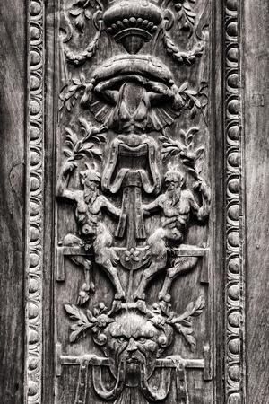 esoterismo: Detalle de la vieja puerta de madera grabada con figuras demoníacas.