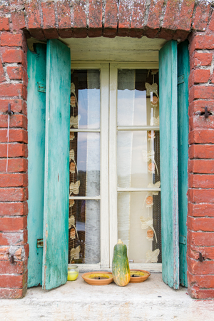 ornamente: Window of a farmhouse with wooden balconies and red brick frame.