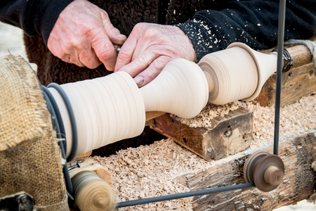 carpenter's sawdust: An artisan carves a piece of wood using an old manual lathe.