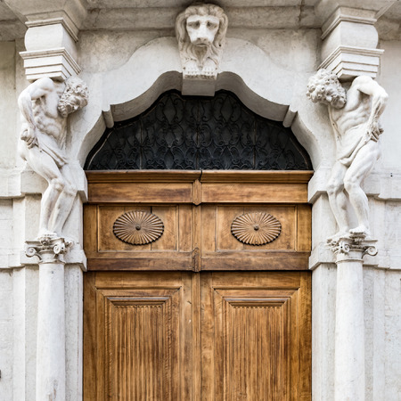 greece granite: Old white stone entrance and wooden portal with statues that support the side columns.