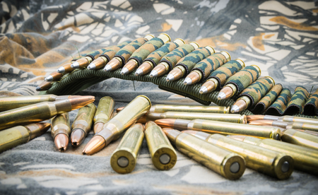 cartridge belt: hollow point ammunitions for rifle on camouflage background. Stock Photo