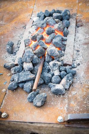 hot temper: barra de hierro puso al calor entre las brasas. Foto de archivo