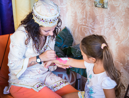 washable: VERONA, ITALY - CIRCA SEPTEMBER 2015: Girl paints a washable tattoo on the arm of a child.