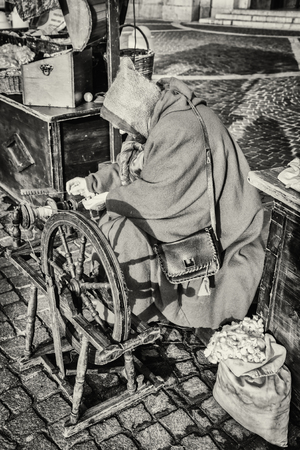 cocoons: Elderly woman uses the cocoons of silkworms to spin using an old spinning wheel of wood.