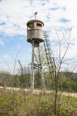 watchtower: Abandoned watchtower isolated by a net topped with barbed wire.