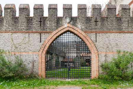 parapet wall: arched entrance of a medieval castle closed by an iron grille gate.