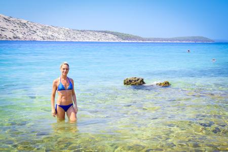 bikini island: Blonde woman in blue bikini in the crystal clear waters of the island of Rab, Croatia.