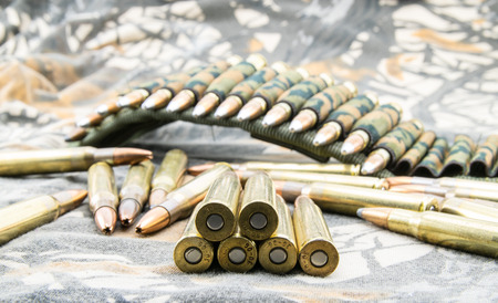 cartridge belt: Hollow-point ammunitions for rifle  on camouflage background. Stock Photo