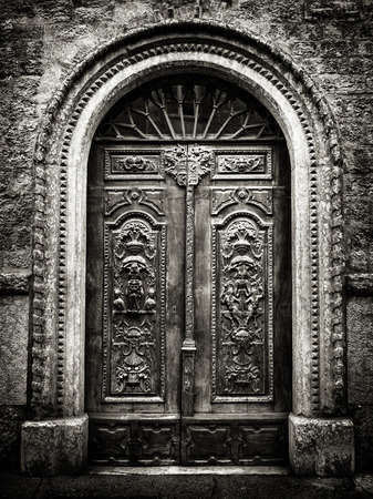 esotericism: Old wooden gate with stone vault engraved with demonic figures. Stock Photo