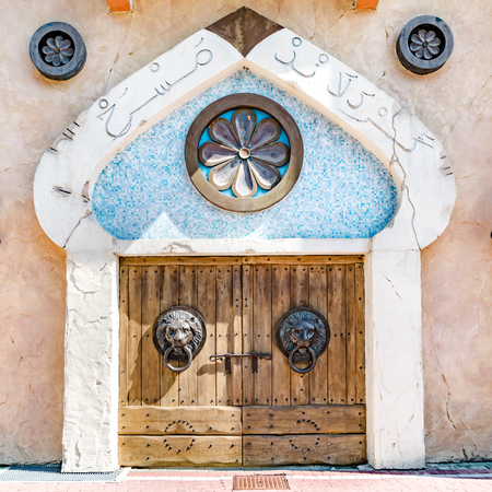 arabic architecture: Typical Arabic architecture entrance with wooden door and door knocker shaped lion head.
