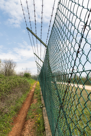 mesh fence: Green mesh fence topped with barbed wire.