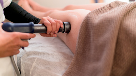 Pressure acoustic wave therapy used to treat the imperfections caused by cellulite. Stock Photo