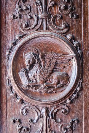 leon con alas: Le�n alado grabado en el portal de madera de una iglesia medieval.