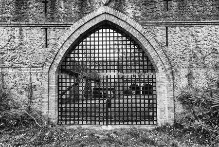 grille: arched entrance closed by an iron grille gate.