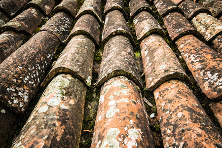 Old red roof tiles on a roof of an old cottage. Stock Photo