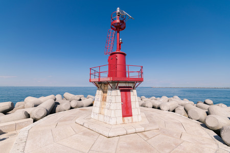 groyne: Red lighthouse that indicates the entrance of the port. Stock Photo