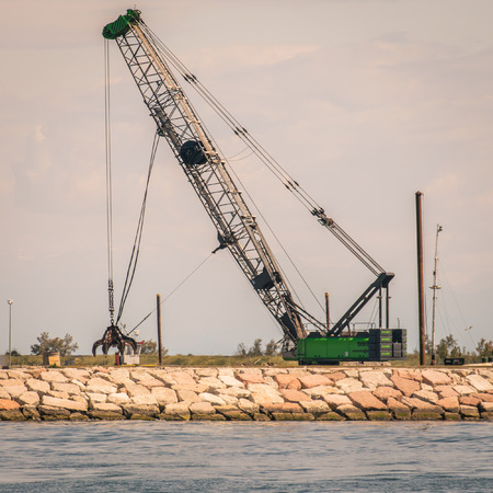 grab: Grab crane in action to build a seawall.