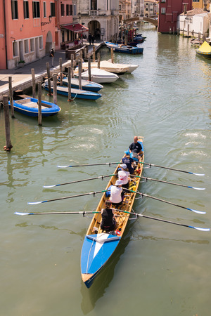synchronous: Venice, Italy - May 20, 2016: Female crew is training on a rowing boat in Venice.