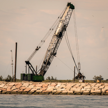 seawall: Grab crane in action to build a seawall.