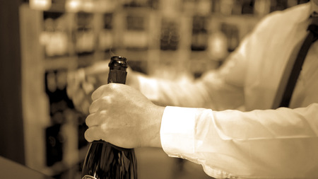uncork: Sommelier uncorks a bottle of sparkling wine in a wine shop. Stock Photo
