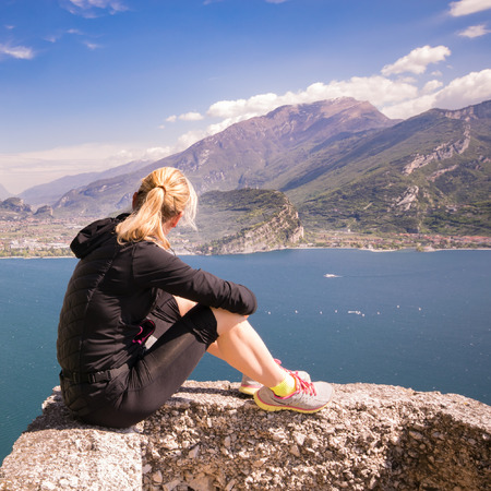 admire: Young sporty woman admire the panorama from the Ponale trail in Riva del Garda, Italy.