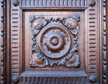church flower: Flower engraved on the wooden portal of a medieval church.