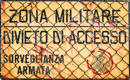 trepassing: Yellow sign that reads in Italian military zone, no entry, armed surveillance.