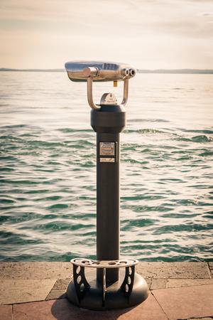 viewing: Coin Operated Binocular viewer next to the waterside promenade in Lazise, lake Garda, Italy.