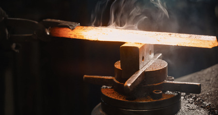 medieval blacksmith: Rod hot iron on the anvil ready to be beaten. Stock Photo