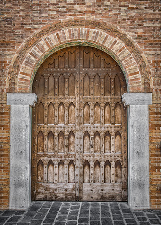 arched: Arched entrance of a medieval palace with carved wooden door. Editorial