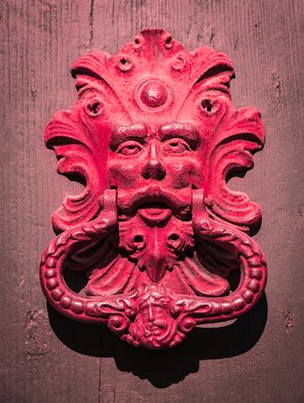 knocker: Red door knocker of an old door.